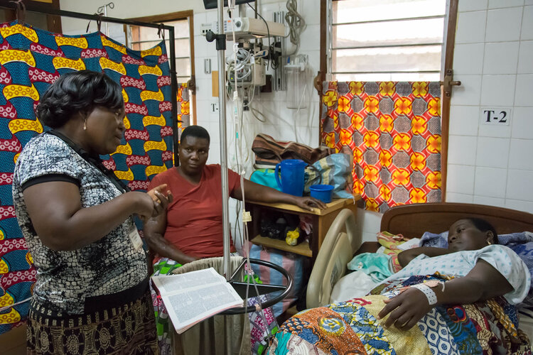 Madame Agathe shares the Gospel with a patient in the maternity ward.